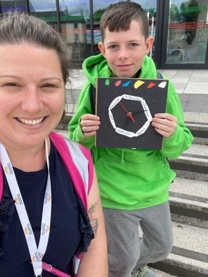 Student Archie with Ms Auger showing off clock design